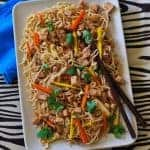 rectangular white plate of noodles meat chunks and vegetables