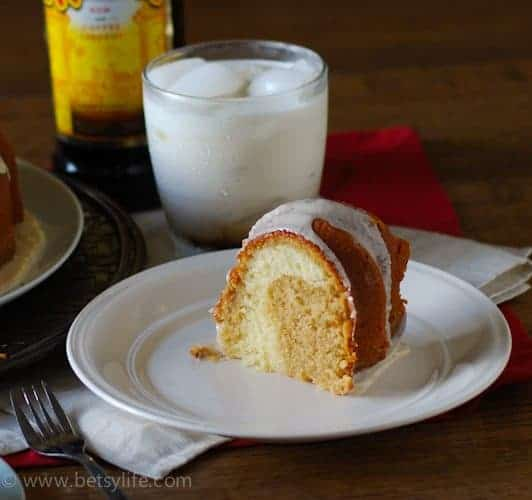 Slice of a yellow and tan swirled bundt cake. White russian cocktail in the background