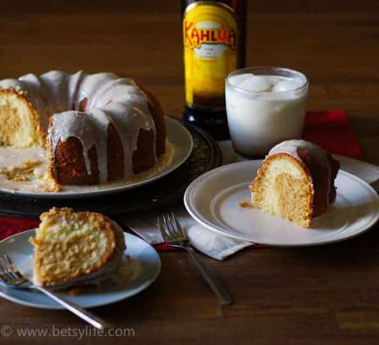 Glazed bundt cake with slices cut out. Two slices on plates in foreground. White russian cocktail and bottle of kahlua in the background