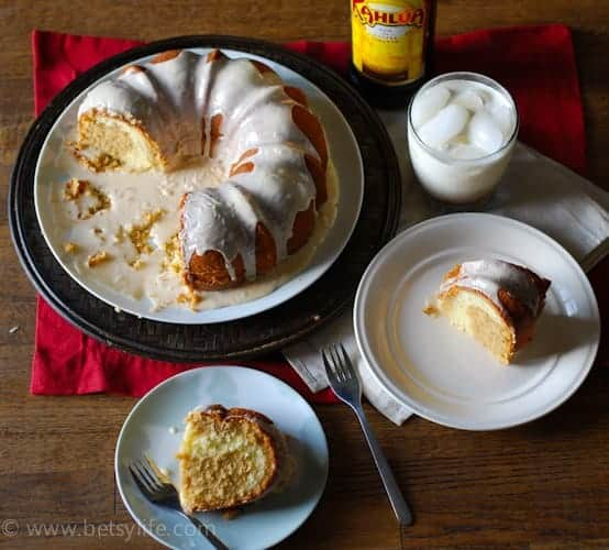 half a glazed bundt cake on a plate. Two slices on small plates next to it with a bottle of kahlua and a white russian cocktail