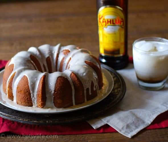 Yellow bundt cake with a white glaze. Bottle of Kahlua in and a white russian cocktail in the background