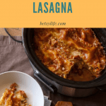 Healthy crock pot lasagna with a slice removed on a white round plate next to a wooden spoon