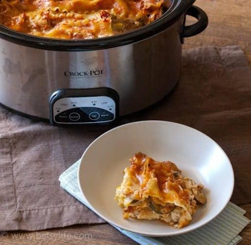 Crock pot lasagna serving in a white bowl next to a crock pot