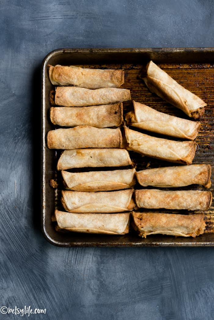 crispy taquitos lined up on a baking sheet