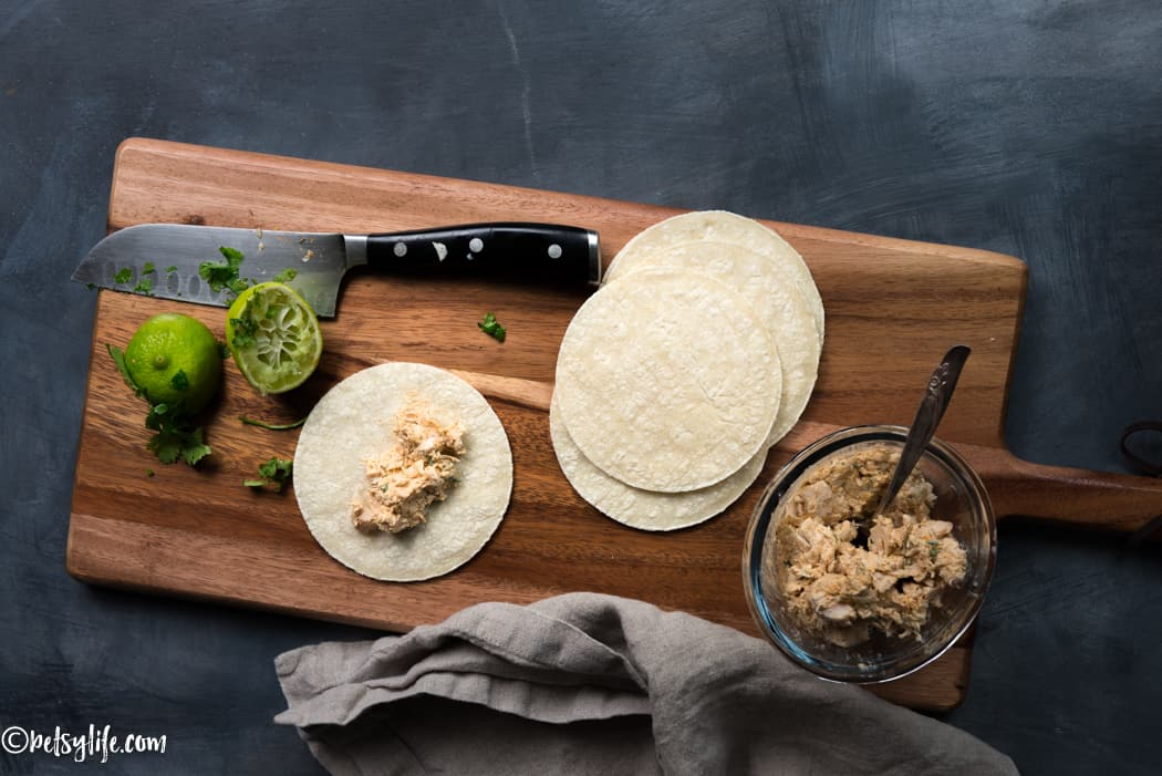 make ahead taquitos being prepared on a wooden board