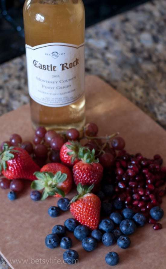 summer berries with a bottle of white wine