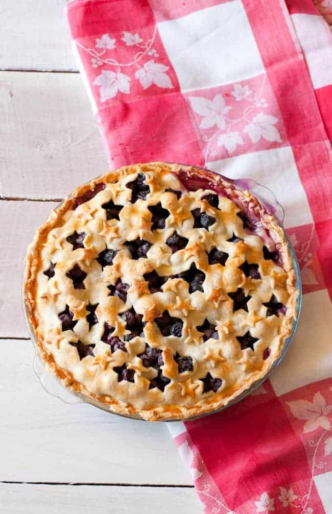 4th of July dessert. Blueberry pie with star shaped cutout crust over a red and white checkered table cloth on a white wood surface