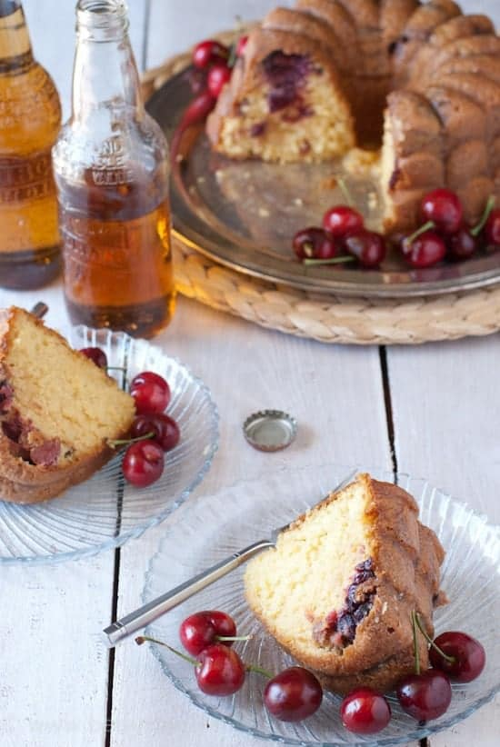 4 Ingredient Cherry & Cream Soda Cake with 2 slices removed on glass plates. Each plate had fresh cherries and a fork with the cake slice. Two bottles of cream soda and rest of the bundt cake out of focus in the background