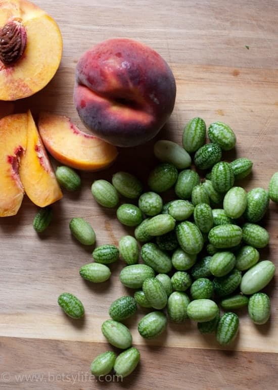 Fresh Peaches and Watermelon Cucumbers on a cutting board