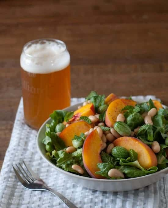 White Bean and Peach Salad with a Lemon-Mint Vinaigrette in a bowl placed on a gray and white striped napkin on a wooden surface. Full glass of beer out of focus in the back left corner of the image. Fork in the foreground.