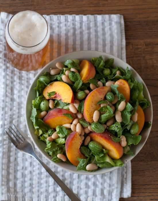 Overhead photo of White Bean and Peach Salad with a Lemon-Mint Vinaigrette in a bowl on a gray and white striped towel with a full glass of beer in the upper left corner and a fork in the lower left corner