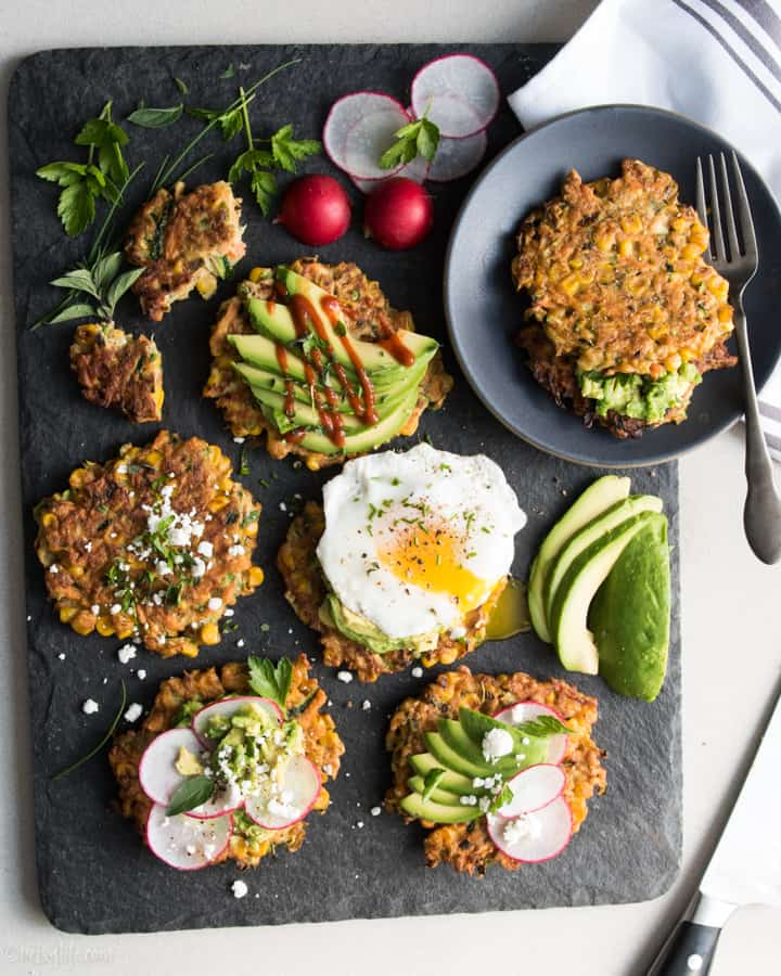 gray serving board with zucchini carrot patties topped with eggs, avocado, hot sauce and radishes