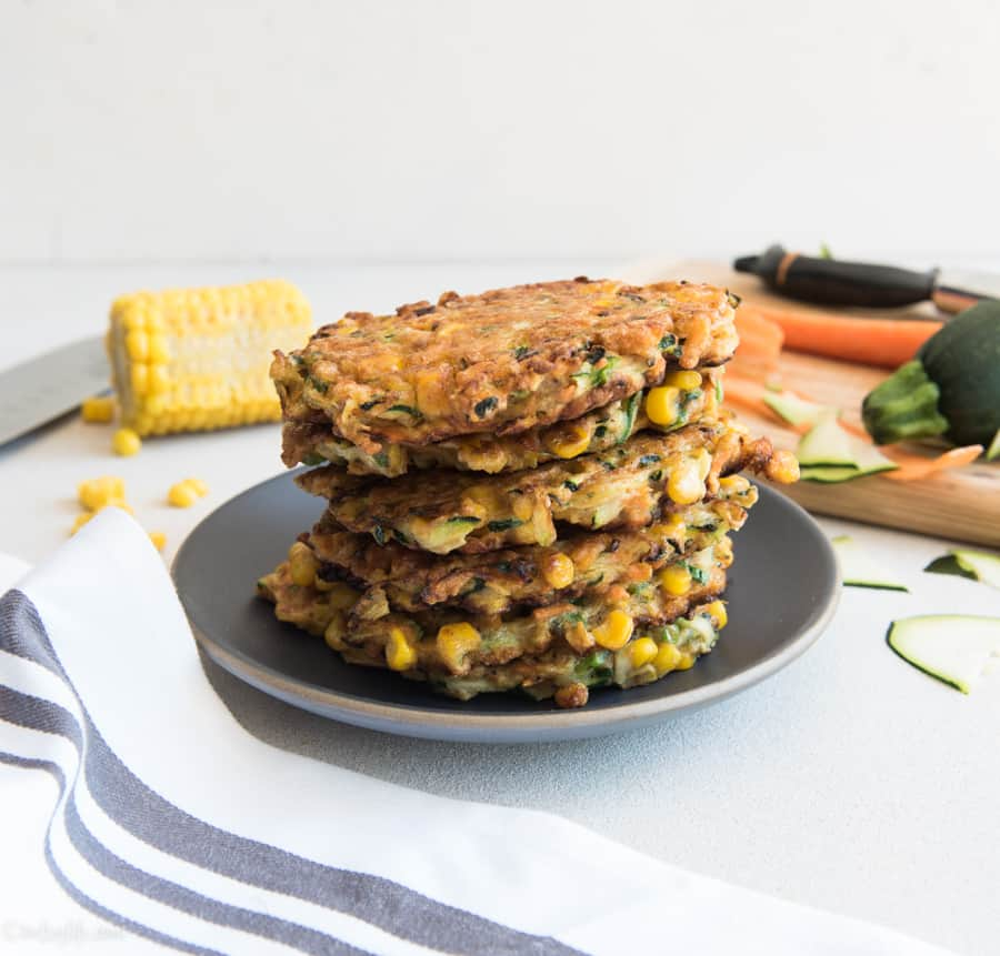 Stack of zucchini carrot and corn fritters on a gray plate