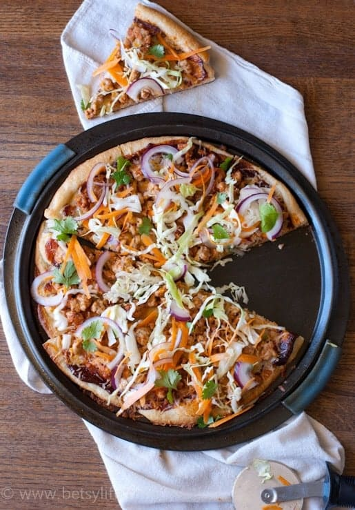 BBq chicken pizza with a slice removed and on the side. Pizza cutter also on the side