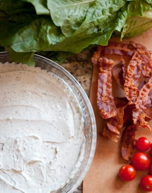 BLT Dip ingredients. Bacon, lettuce, tomatoes and herb cream cheese spread into the bottom of a round glass dish