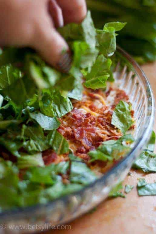 Hand sprinkling lettuce on top of layers of blt dip