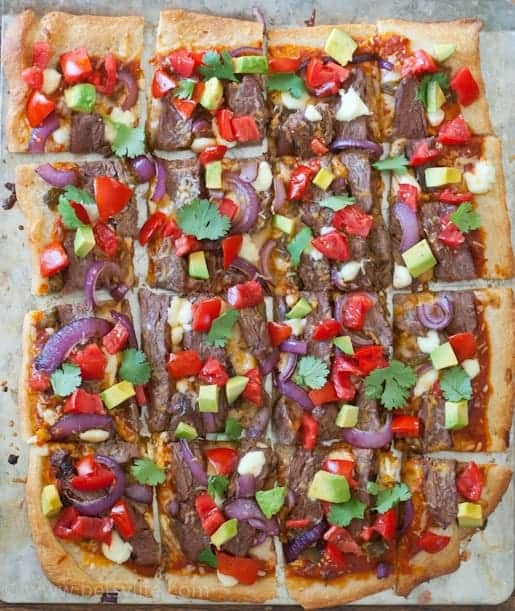 Carne Asada Pizza photographed from overhead. Rectangular shaped, and cut into squares. Topped with carne asada, grilled red onions, peppers and cilantro