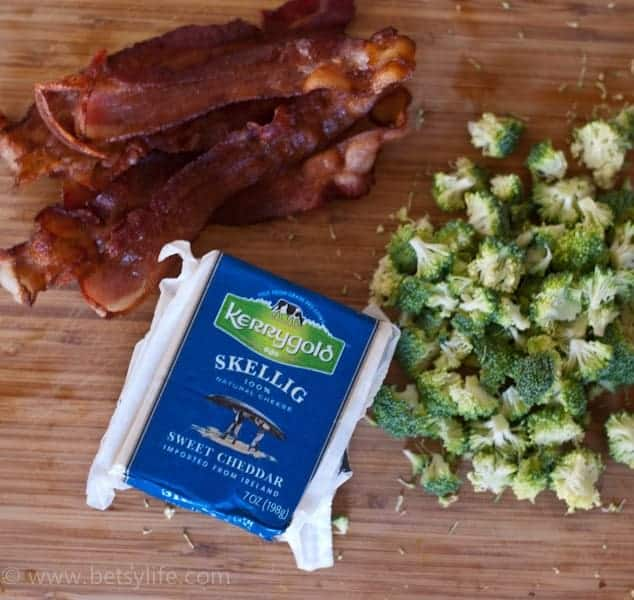 Cooked bacon, diced broccoli and a square of Skellig cheese on a cutting board