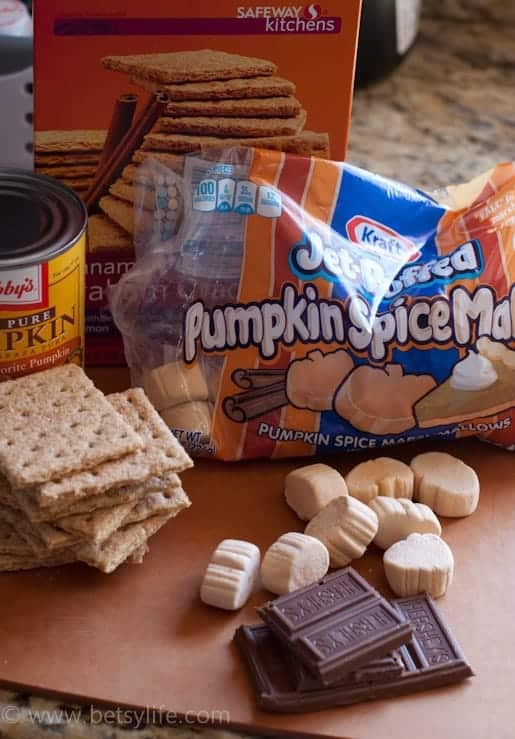 ingredients for pumpkin smores on a wood cutting board. pumpkin spice marshmallows, cinnamon graham crackers, pumpkin pie filling, chocolate bars