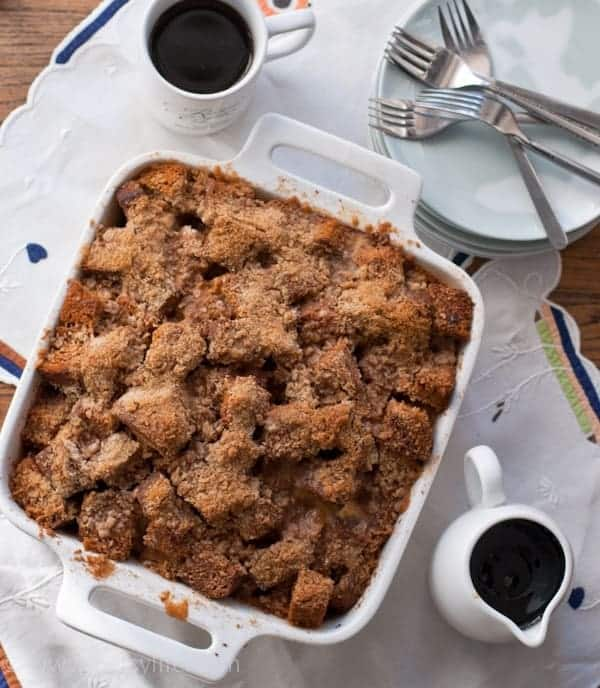 Gingerbread french toast casserole in a white square baking dish with two cups of coffee