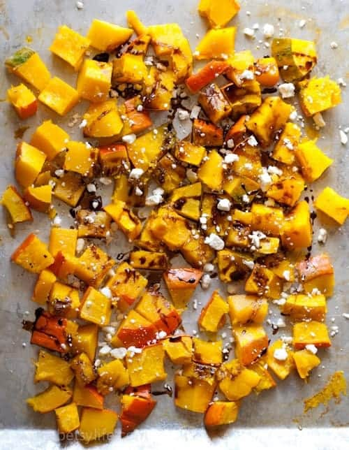 Kabocha squash diced on a baking sheet. Drizzled with balsamic and feta