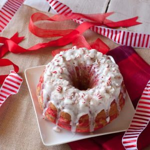 Peppermint Candy Bundt Cake on a white square plate with white and red ribbons around it