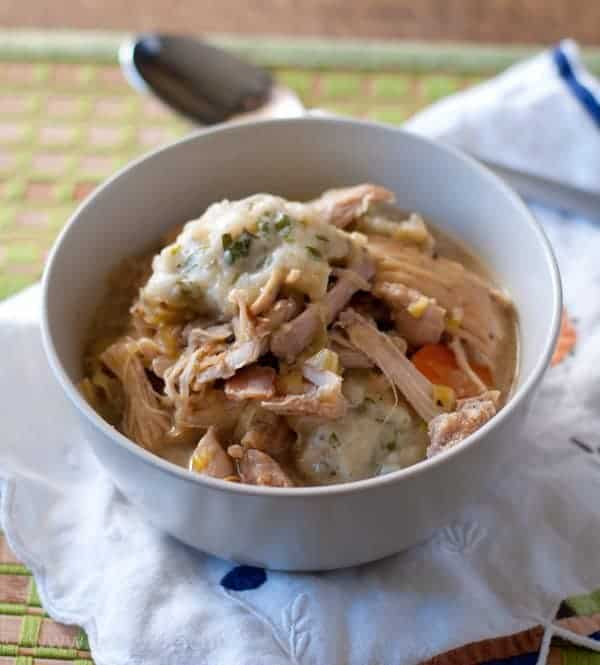 Serving of Chicken with Garlic and Herb Dumplings in a light colored bowl on a white napkin