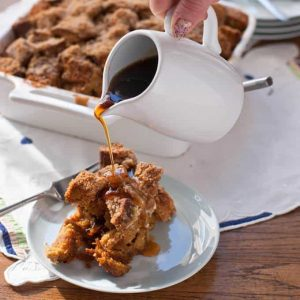 Gingerbread French Toast Casserole serving with hand pouring syrup from a small white pitcher
