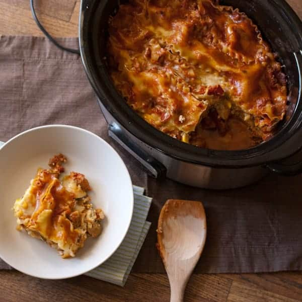 crock pot with lasagna and lasagna on white plate