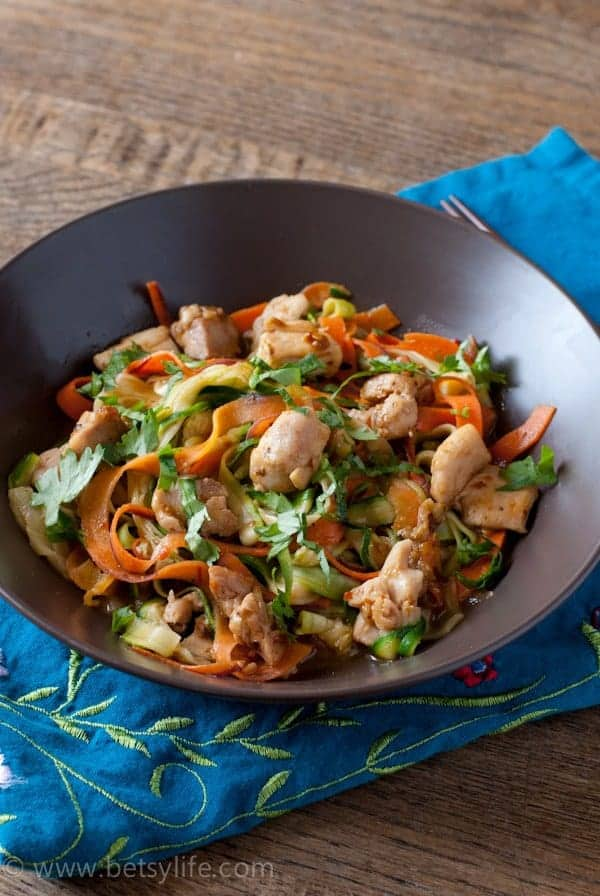 brown bowl of chicken stir fry with veggie noodles on a blue napkin