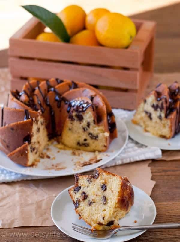 Dark Chocolate Orange Cake slices on two plates with a crate of oranges and remainder of cake in the background