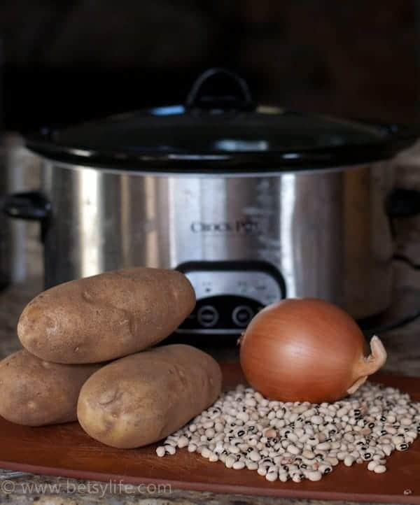 crock pot next to a cutting board with dried peas, potatoes and onions