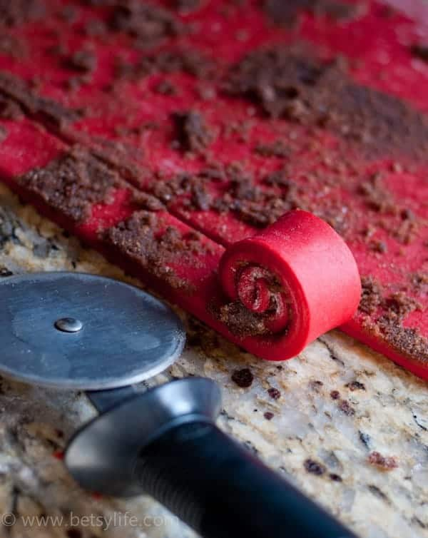 Pizza cutter next to rolled out red dough that's being rolled up with cinnamon and sugar on the inside