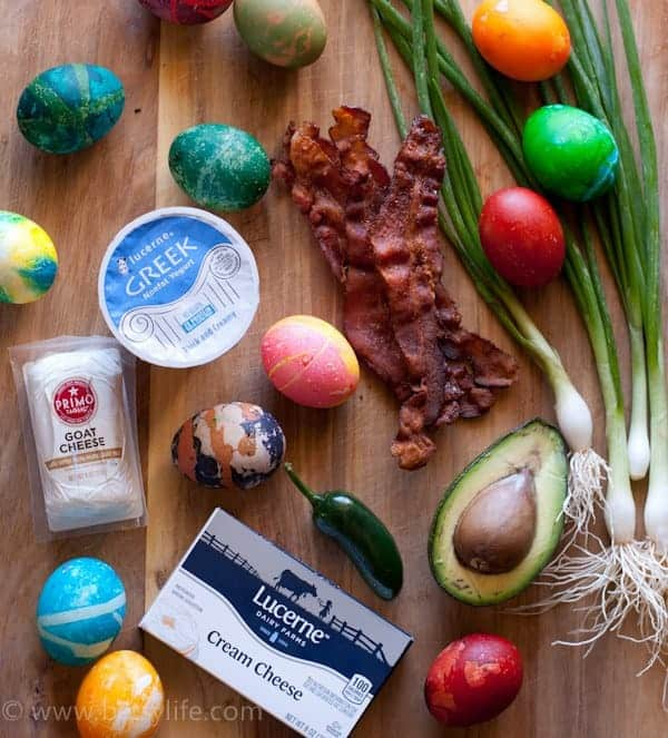 Photo of brightly colored Easter eggs with bacon, scallions, half and avocado, greek yogurt, goat cheese and cream cheese