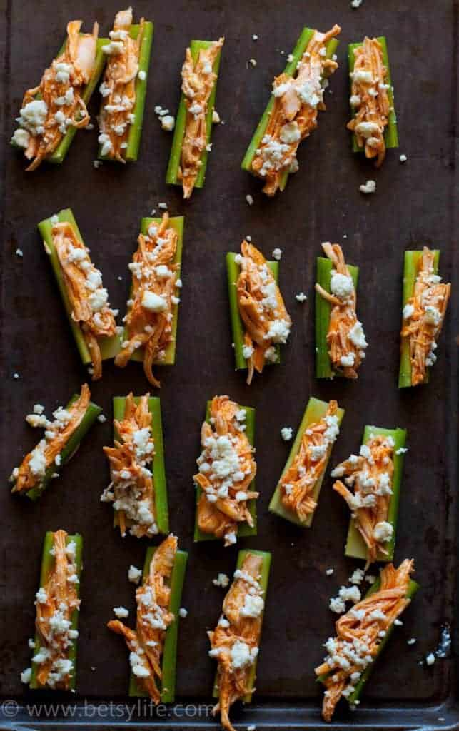 pan of celery sticks filled with chicken and cheese crumbles
