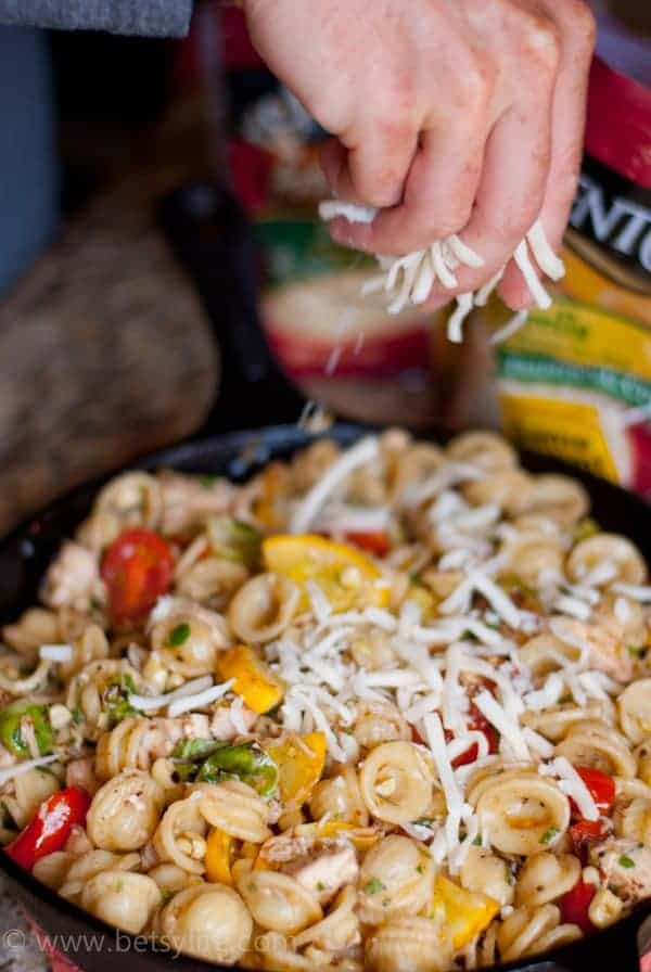 hand sprinkling cheese over vegetables and Pasta