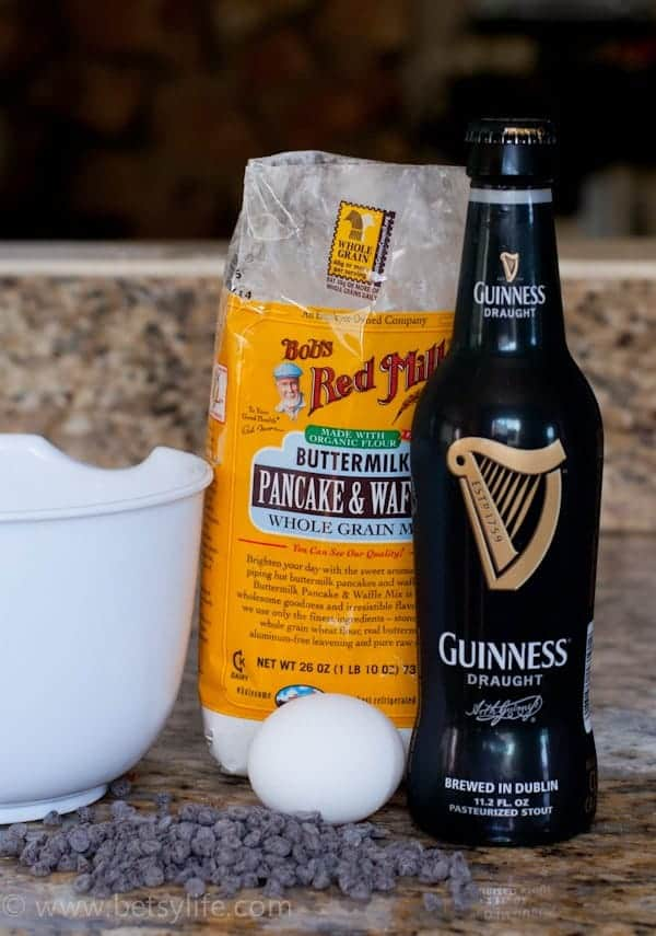 bag of pancake mix next to a bottle of Guinness stout, an egg and a pile of chocolate chips