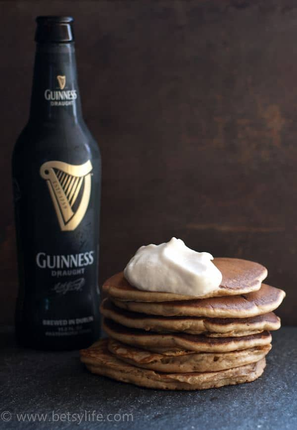 Stack of Guinness stout pancakes topped with Bailey's Irish cream whipped cream dollop next to a bottle of beer
