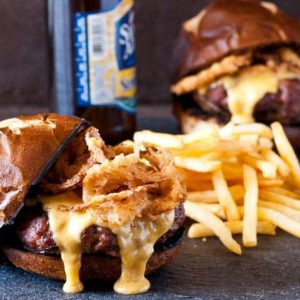 burger on toasted bun with fries and beer