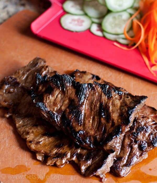 grilled flank steak on a cutting board next to another cutting board covered in sliced vegetables