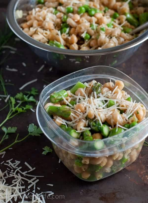 Pasta salad with asparagus and peas in a small tupperware container next to a bowl of more pasta salad