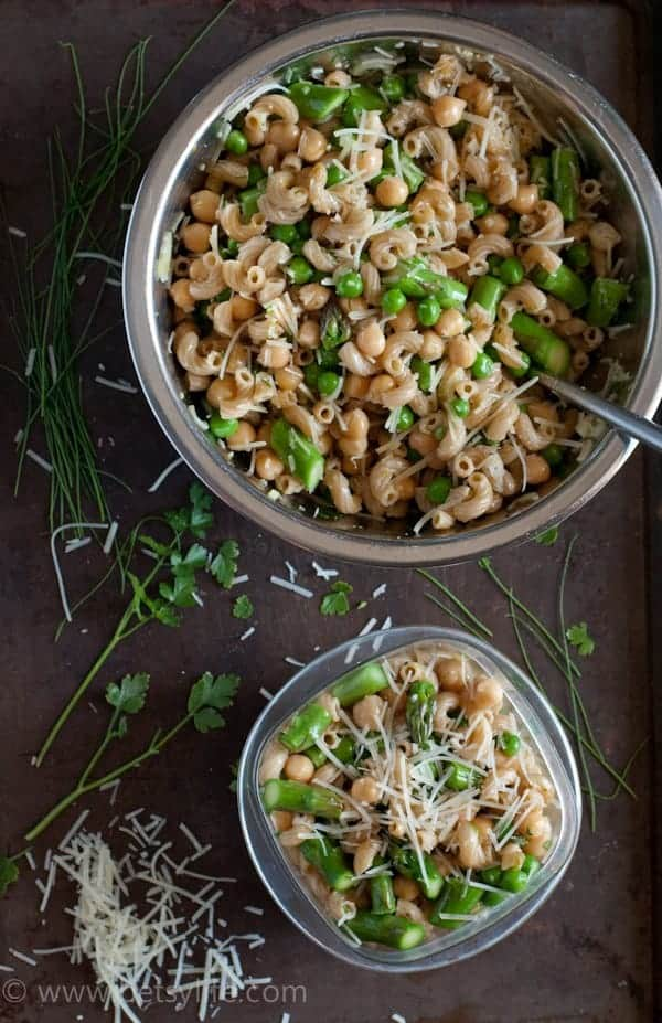 Spring Pea and Asparagus Pasta Salad in a large bowl next to a smaller tupperware container