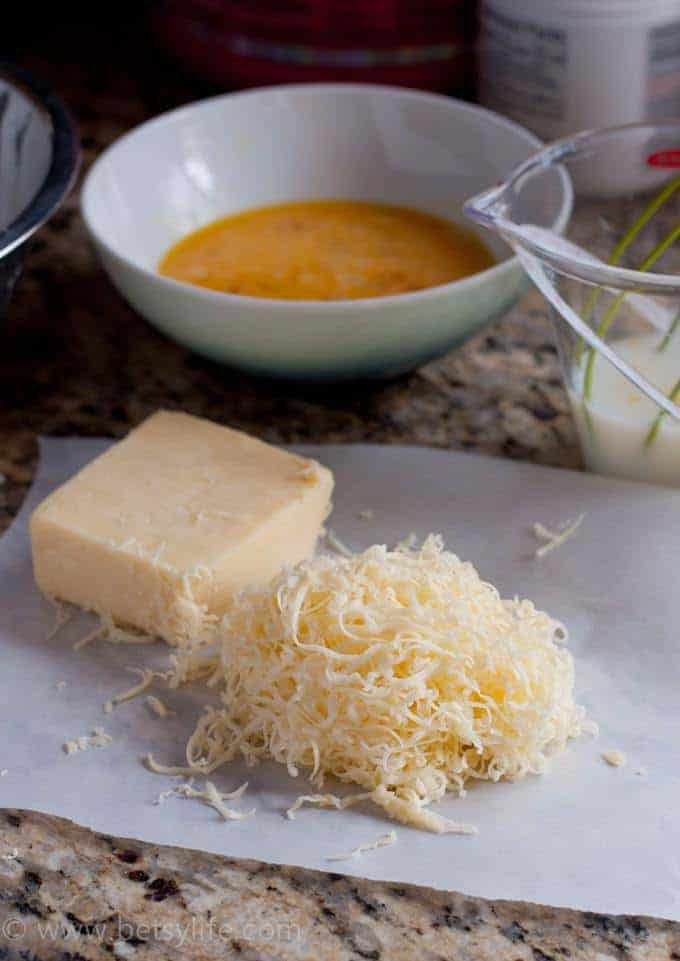 Pile of shredded white cheddar cheese next to the block of cheese it was shredded from. Bowl of whisked eggs and a liquid measuring cup full of milk in the background