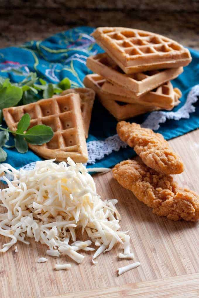 Stack of 4 waffles with an additional waffle in front. Two fried chicken fingers and a pile of shredded white cheese on a blue floral print linen.