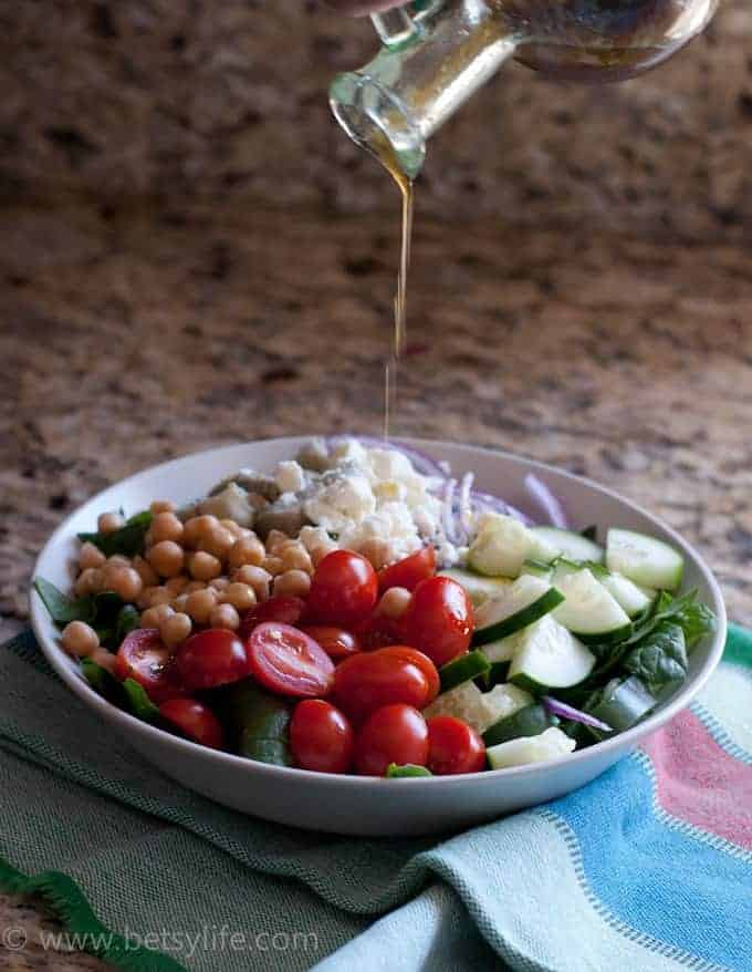 olive oil dressing drizzling over a garbanzo bean salad