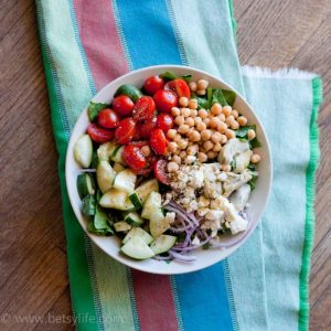 Greek garbanzo bean salad in a bowl on a green, red and blue striped linen
