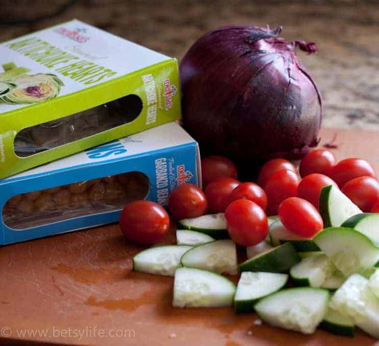 tomatoes, cucumbers, artichoke hearts, red onion and garbanzo beans on a wooden cutting board