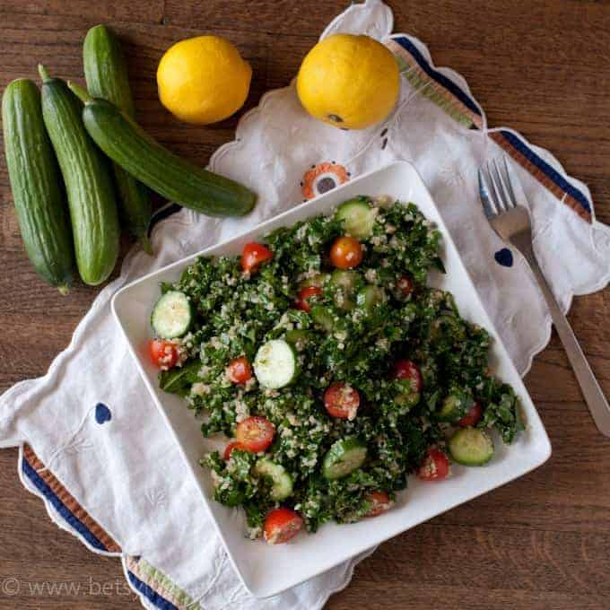 Kale Quinoa Tabbouleh Salad on a square white plate next to cucumbers and lemons