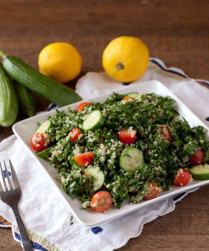 Kale Quinoa Tabbouleh Salad on a square white plate with cucumbers and lemons in the backgroun d