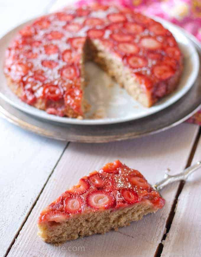 Almond Strawberry Upside Down Cake with a sliced removed in the foreground